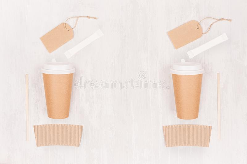 Coffee branding mockup - two brown paper cups with blank label, card, sugar, copy space on white wood board, top view. royalty free stock image