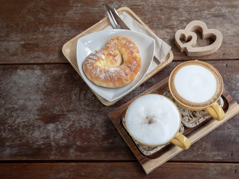 Coffee and bread. Flat lay two hot coffee cups and sweet bread on white plate on wooden tray with wooden twin heart on wooden table background royalty free stock photo