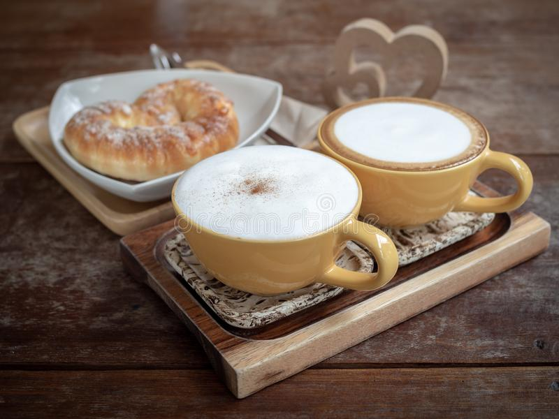 Coffee and bread. Two hot coffee cups and sweet bread on white plate on wooden tray with wooden twin heart on wooden table background royalty free stock photo