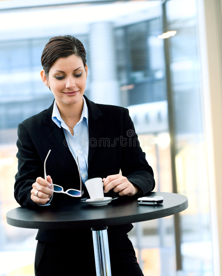 Coffee Break. Young businesswoman having break and drinking coffee in office stock image
