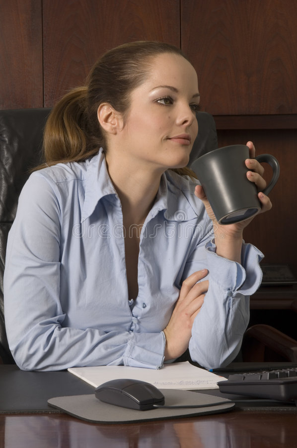 Coffee break. Female employee takes break to enjoy her morning coffee and think the day ahead stock photo