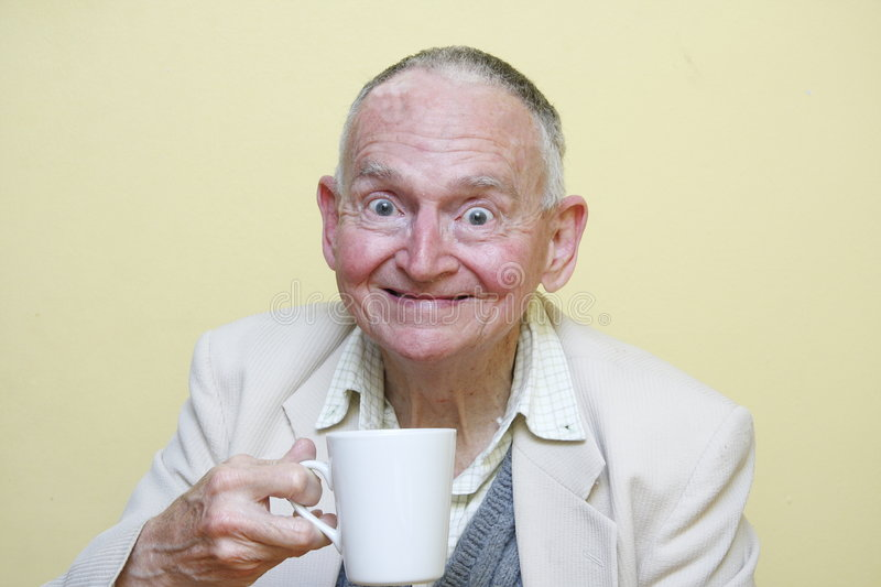 Coffee break. Elderly man about to drink some coffee out of a white mug stock photos