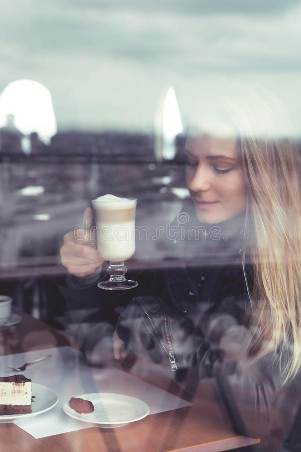 Coffee break. Beautiful blond woman sitting in cafe and enjoying latte with tasty sweet dessert, coffee break, urban lifestyle of young people stock photos