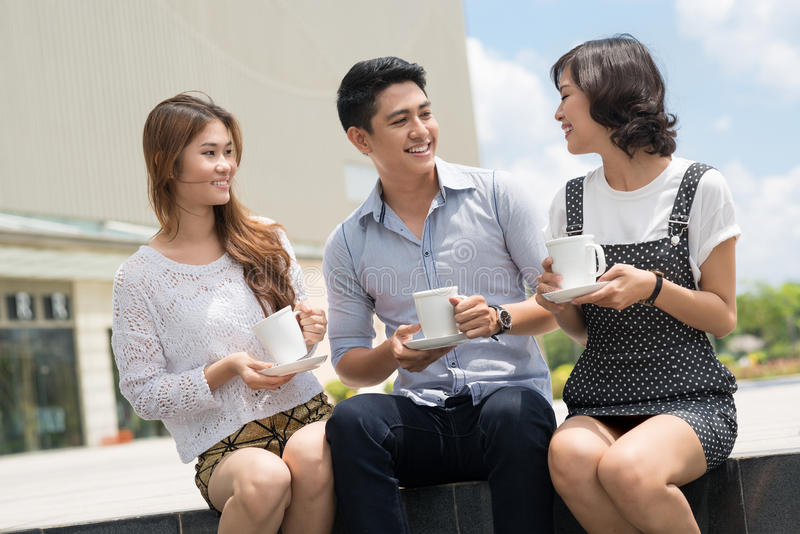 Coffee break chatting. Friend's team talking and drinking coffee outdoors stock images