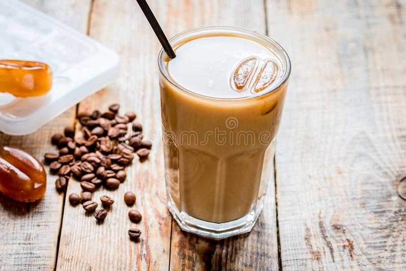 Coffee break with cold iced latte and beans on wooden table back. Coffee break with cold iced latte and beans in caffee on wooden table background royalty free stock photography