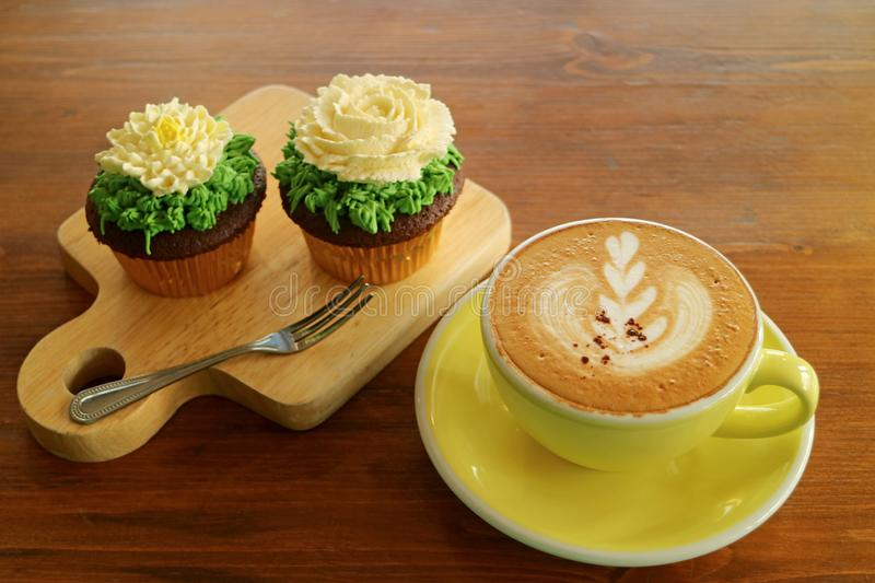 Coffee break with a cup of hot cappuccino and two cupcakes topped with flower shaped whipped cream royalty free stock image