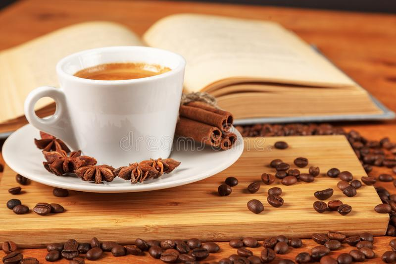 White Cup of coffee espresso surrounded by of roasted coffee beans, cinnamon, anise and an open book on a wooden table stock photos