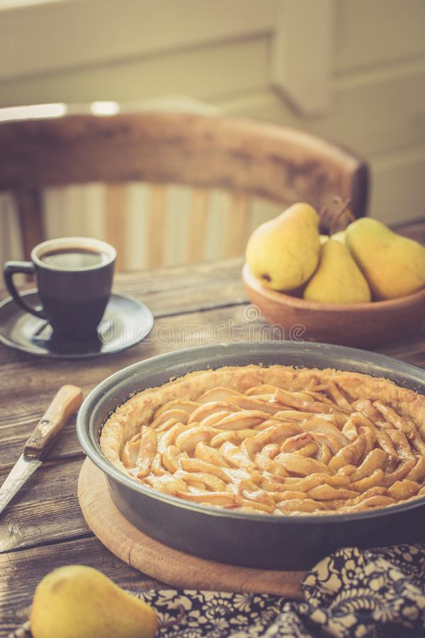 Coffee break with french pear tart, vintage toned. Coffee break or breakfast with french pear tart and coffee, vintage toned royalty free stock image