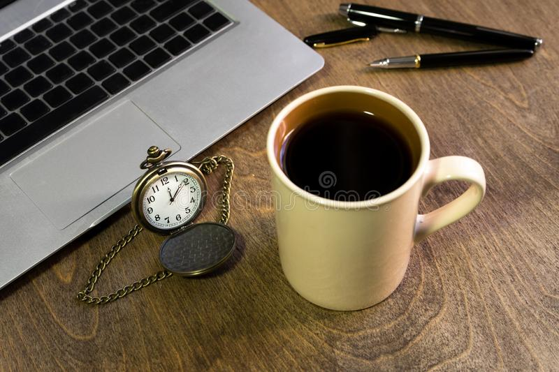 Coffee break! Home office interior in loft space. Workplace with wooden table, office supplies, documents, organizer and laptop. M stock photo