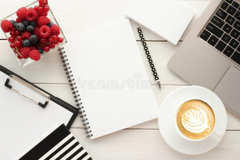 Office table with cup of coffee and fresh berries royalty free stock photography