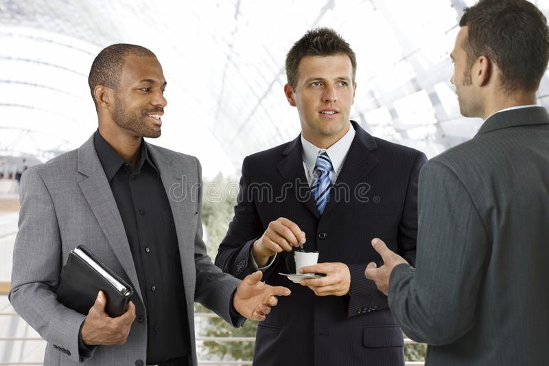 Coffee-break at office lobby. Young businessmen having coffee-break at office lobby, talking, drinking coffee stock photography