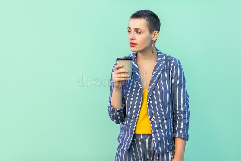 Coffee break. Portrait of dreaming resting beautiful with short hair young woman in striped suit standing,take pause and drinking royalty free stock image