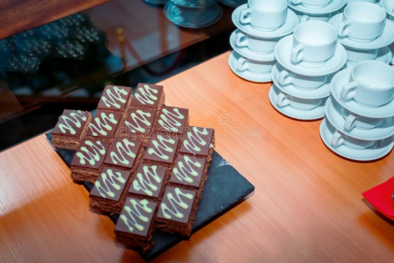 Coffee break served on the table – pieces of chocolate cake on black stone tray stock photo