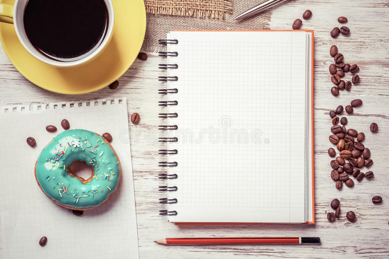 Coffee break with snack. Opened notepad and cup of coffee with donut on wooden table royalty free stock photo