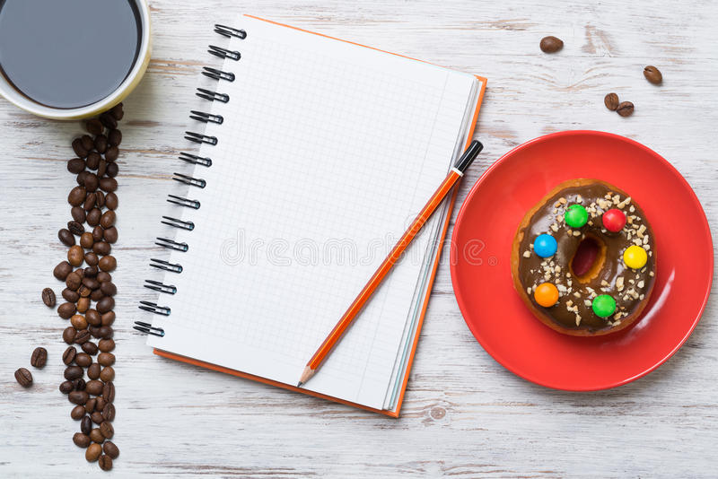 Coffee break with snack. Opened notepad and cup of coffee with donut on wooden table stock images
