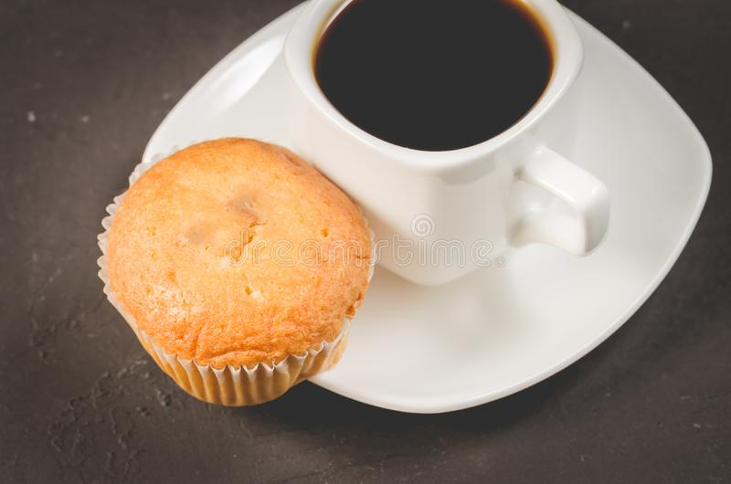 Coffee break. White cup of the hot black coffee and cupcake on a dark background. Breakfast concept royalty free stock photo