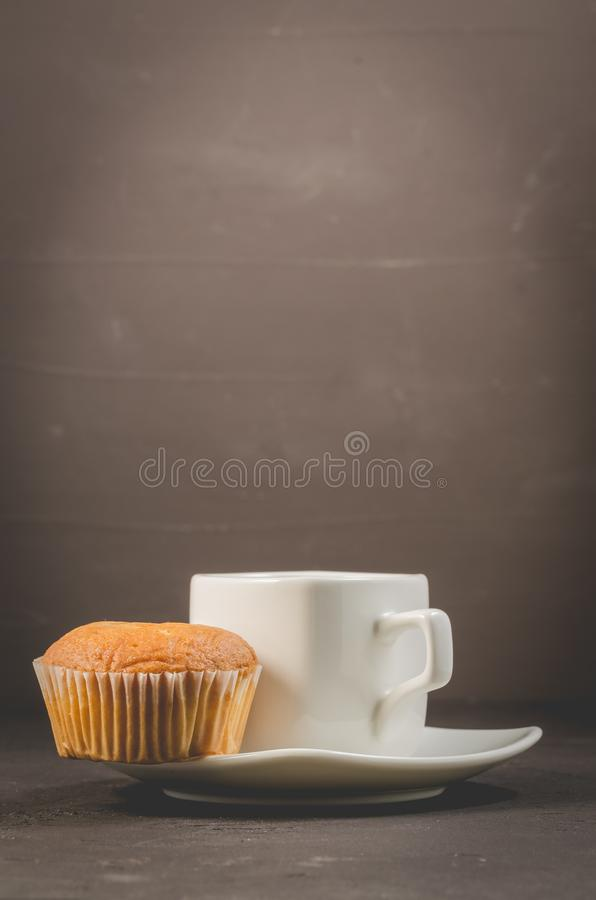 Coffee break. White cup of the hot black coffee and muffin. Breakfast concept stock images