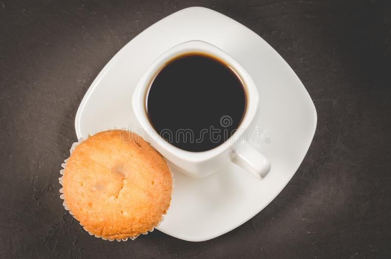 Coffee break. White cup of the hot black coffee and muffin, top view. Breakfast concept stock photography