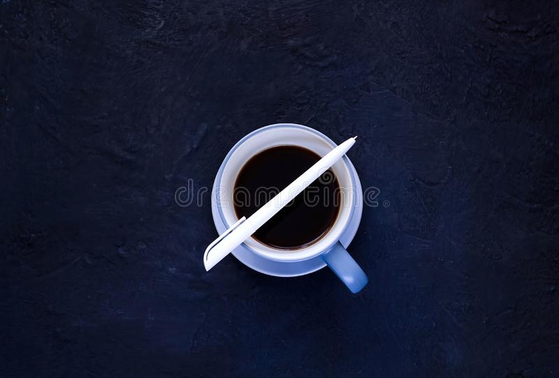 Coffee break, white pen and blue ceramic cup with coffee on dark background, isolated, copy space, closeup,flat lay royalty free stock photos