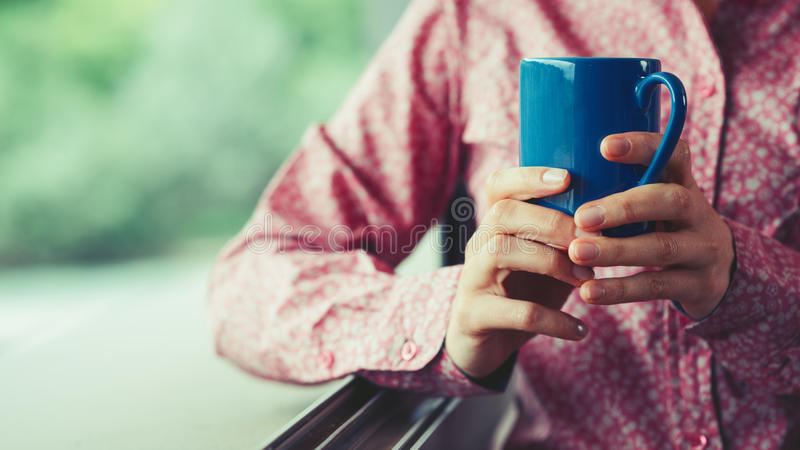Coffee break. Woman at window holding a cup and having a relaxing coffee break, hands close up royalty free stock photography