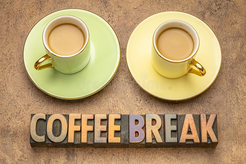 Coffee break word abstract in wood type. Coffee break word abstract in vintage letterpress wood type with two cups of coffee royalty free stock photography