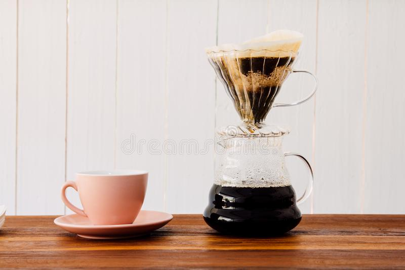 Coffee brewing equipment and color living coral cup on table wooden bar counter royalty free stock photo