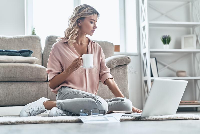 Coffee brings fresh ideas. Beautiful young woman holding a cup and using laptop while sitting on the floor at home royalty free stock images