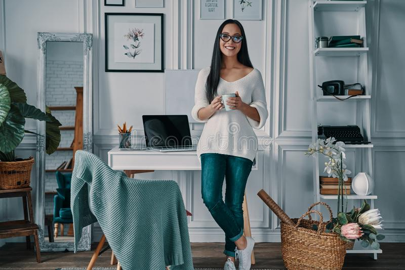 Coffee brings fresh ideas. Beautiful young woman looking at camera and smiling while standing in home office stock photo