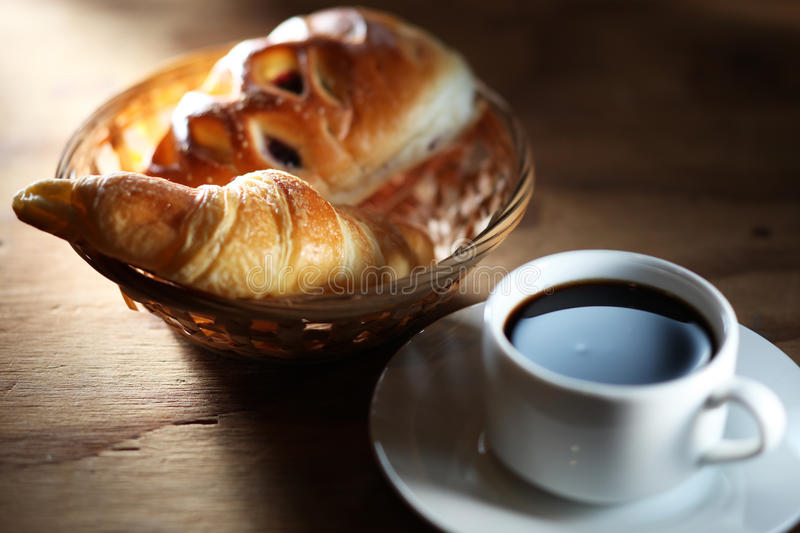 Coffee and bun. On wooden table with mood lighting