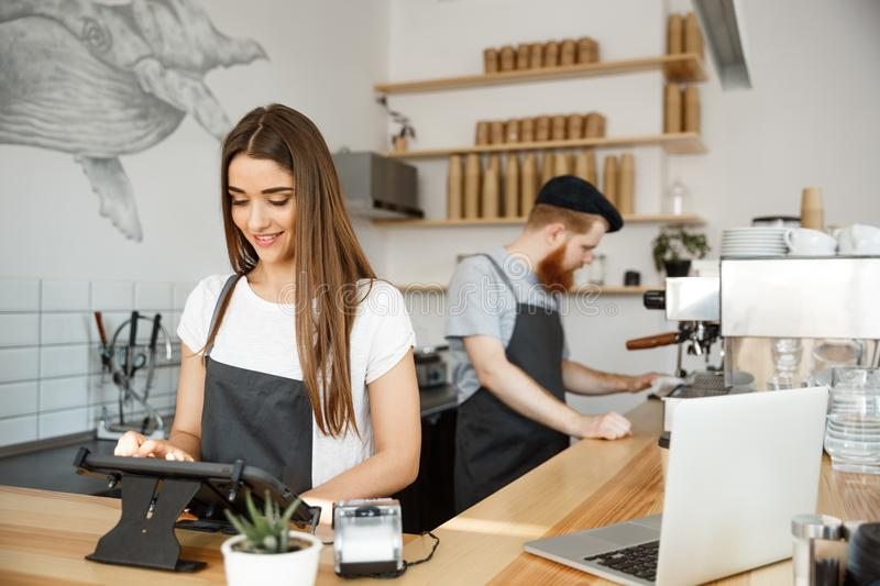 Coffee Business Concept - beautiful caucasian bartender barista or manager Posting order in digital tablet menu at royalty free stock images