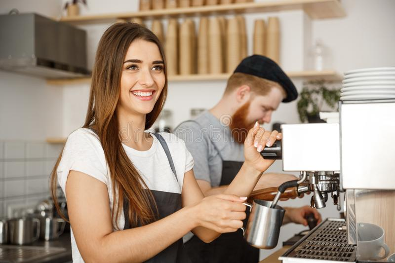 Coffee Business Concept - portrait of lady barista in apron preparing and steaming milk for coffee order with her. Partner while standing at cafe stock photo