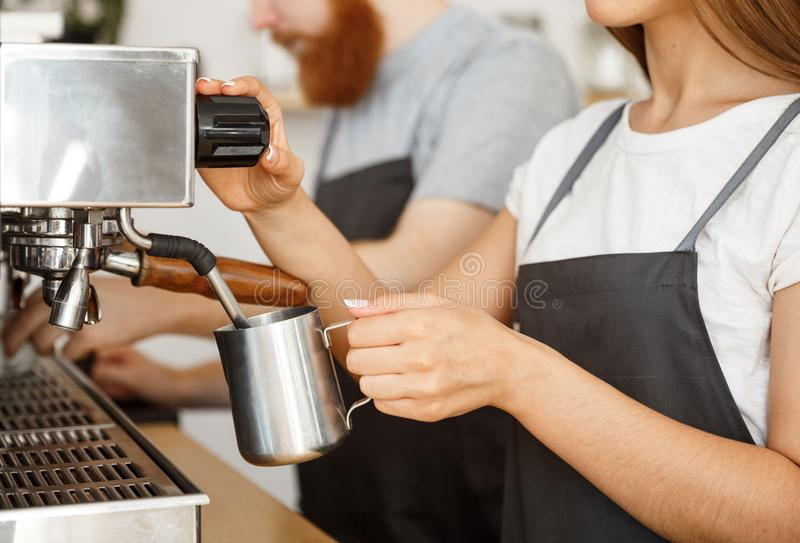 Coffee business concept - portrait of lady barista in apron preparing and steaming milk for coffee order with her stock images