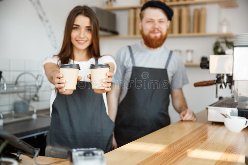 Coffee Business Concept - Positive young bearded man and beautiful attractive lady barista couple giving take away cup royalty free stock images