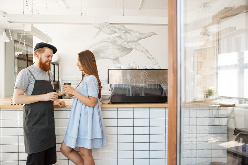 Coffee Business Concept - young smart bearded bartender enjoy talking and giving take away cup of coffee to pretty royalty free stock photos