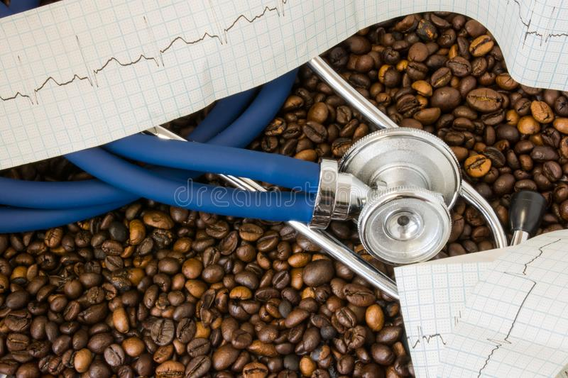 Coffee or caffeine and heart arrhythmias irregular heartbeat. Stethoscope and ECG tape on background of coffee beans. Effect and royalty free stock images