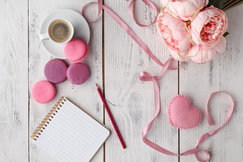 Coffee, cake macaron, clean notebook, eyeglasses and flower on pink table from above. Female working desk. Cozy breakfast. Flat la stock images