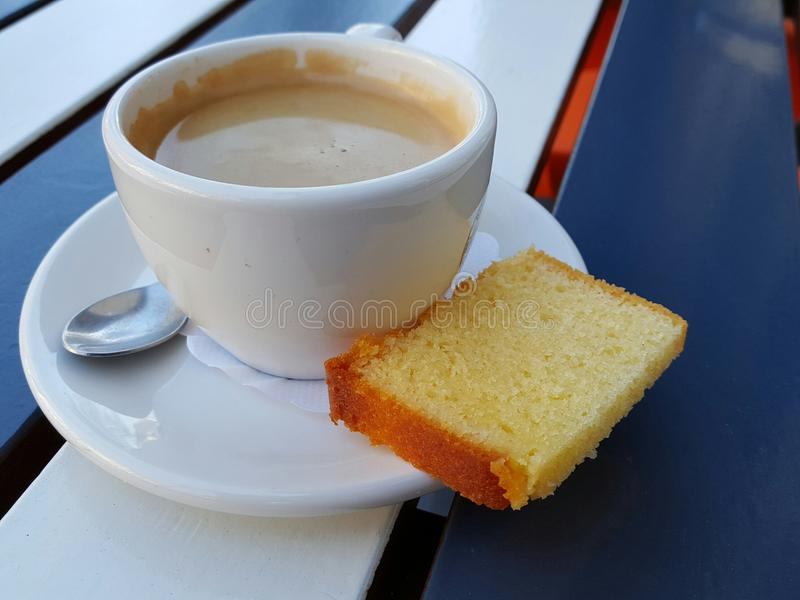 Coffee with cake. Coffee in white porcelain cup and sauces with slice of yellow pound cake with spoon on blue and white slat tabletop stock images