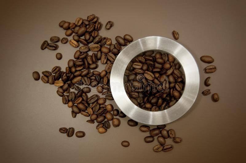 Coffee canister lid and coffee beans scattered on the table stock photos