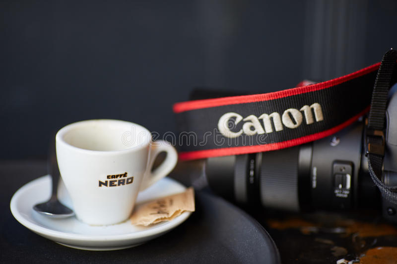 Coffee and canon camera. Coffee cup and a canon dslr camera royalty free stock photo