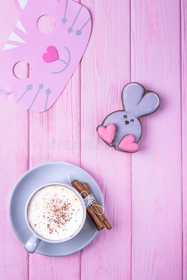 Coffee cappuccino with cinnamon and gingerbread rabbit with heart on a pink wooden background. Happy Valentine`s Day! royalty free stock photo