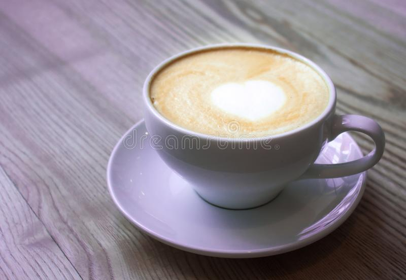 Cap of cappuccino. Coffee cappuccino in white mug on wooden table, neon purple lilac tone background. Heart latte art concept royalty free stock photo