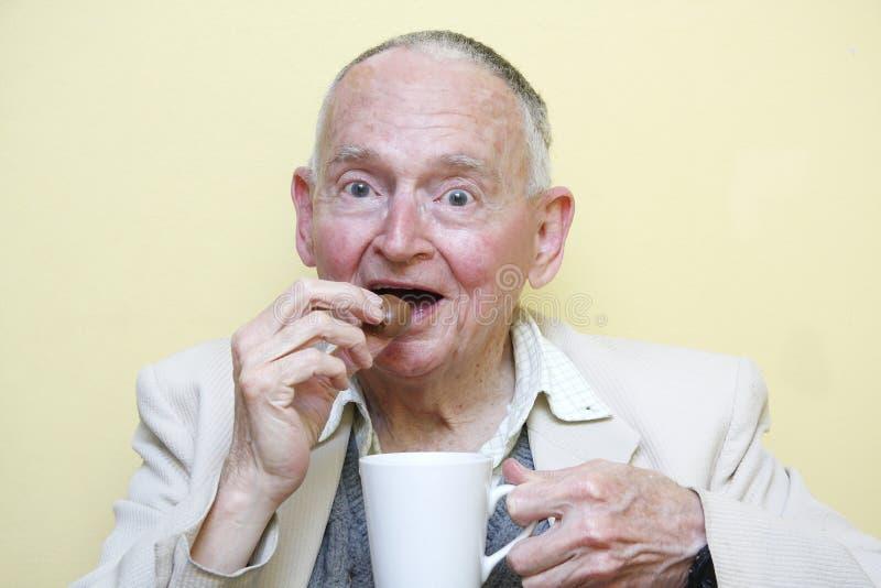 Coffee & chocolate. Elderly man drinking coffee and eating chocolate royalty free stock photos