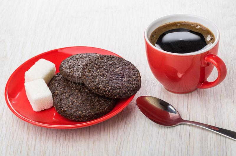 Coffee, chocolate cookies with airy rice, sugar cubes, spoon. Coffee in red cup, chocolate cookies with airy rice, sugar cubes in saucer, spoon on wooden table royalty free stock photo