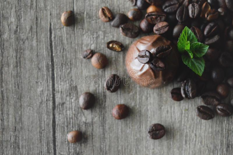 Coffee chocolate pralines. Chocolate candy with coffee filling. Pralines, coffee beans on wooden table. With mint leaves stock photography