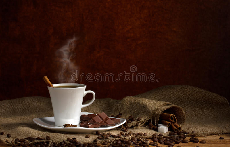 Coffee and chocolate. Coffee with steam and slice of chocolate on saucer, and cubes sugar and coffee beans on burlap wooden table on dark brown background royalty free stock photography