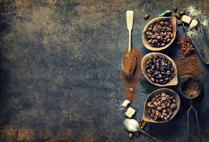 Coffee composition. Top view of three different varieties of coffee beans on dark vintage background royalty free stock photography