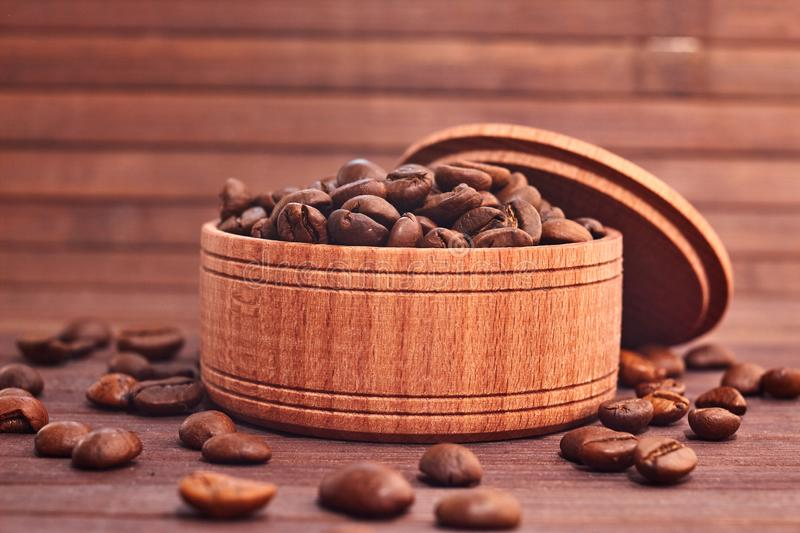 Coffee composition on a wooden background. Grains of coffee in a wooden jar. Lattice coffee beans close-up on a wooden surface. Co royalty free stock photos