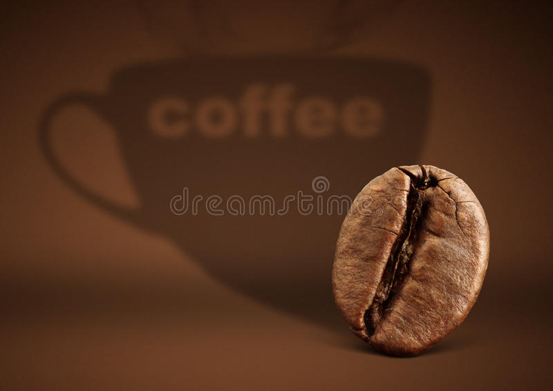 Coffee concept, bean with cup shadow on brown background royalty free stock photography