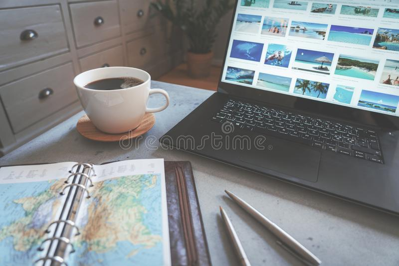 Coffee on concrete table with travel map, pens and laptop with travel destinations as backdrop royalty free stock photos
