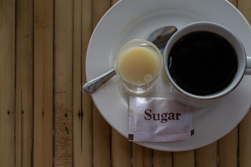Coffee and condensed milk and sugar. Morning breakfast table top view photo. Rustic wooden table with coffee cup royalty free stock photography